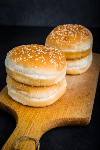 Buns with sesame for hamburger on a kitchen board